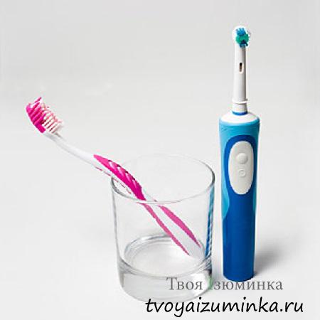 Обычная и электрическая зубные щетки.