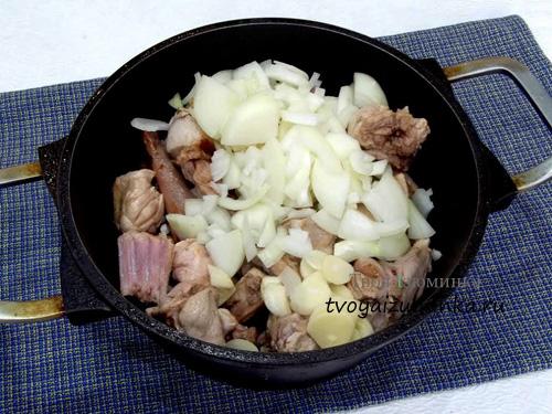 Нарезанные лук и чеснок в кастрюле с мясом кролика
